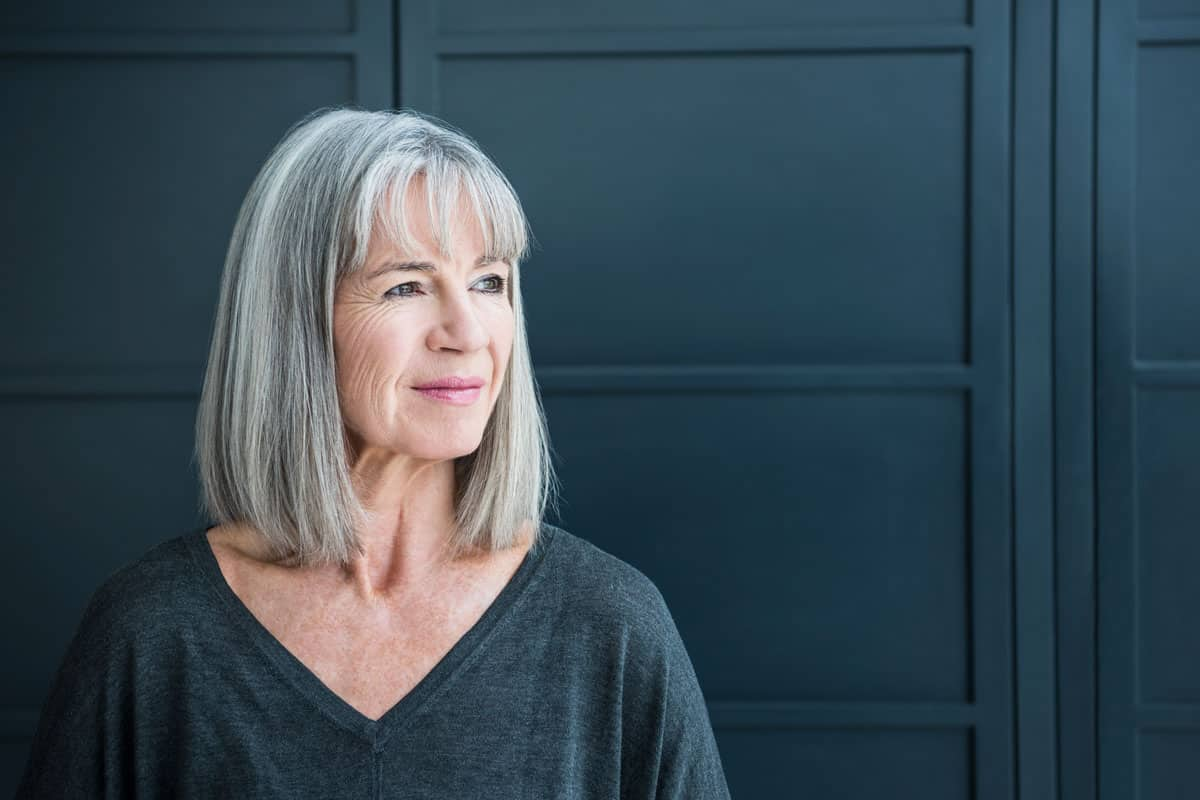An elderly woman in a gray shirt standing on a black door with a bob hair cut, 25 Awesome Bob Hairstyles for Women Over 60