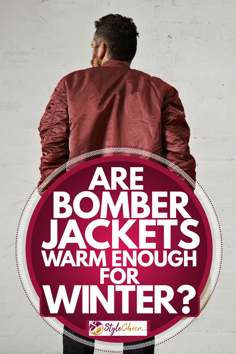 A man wearing a bomber jacket and holding a helmet while staring at a gray wall, Are Bomber Jackets Warm Enough For Winter?