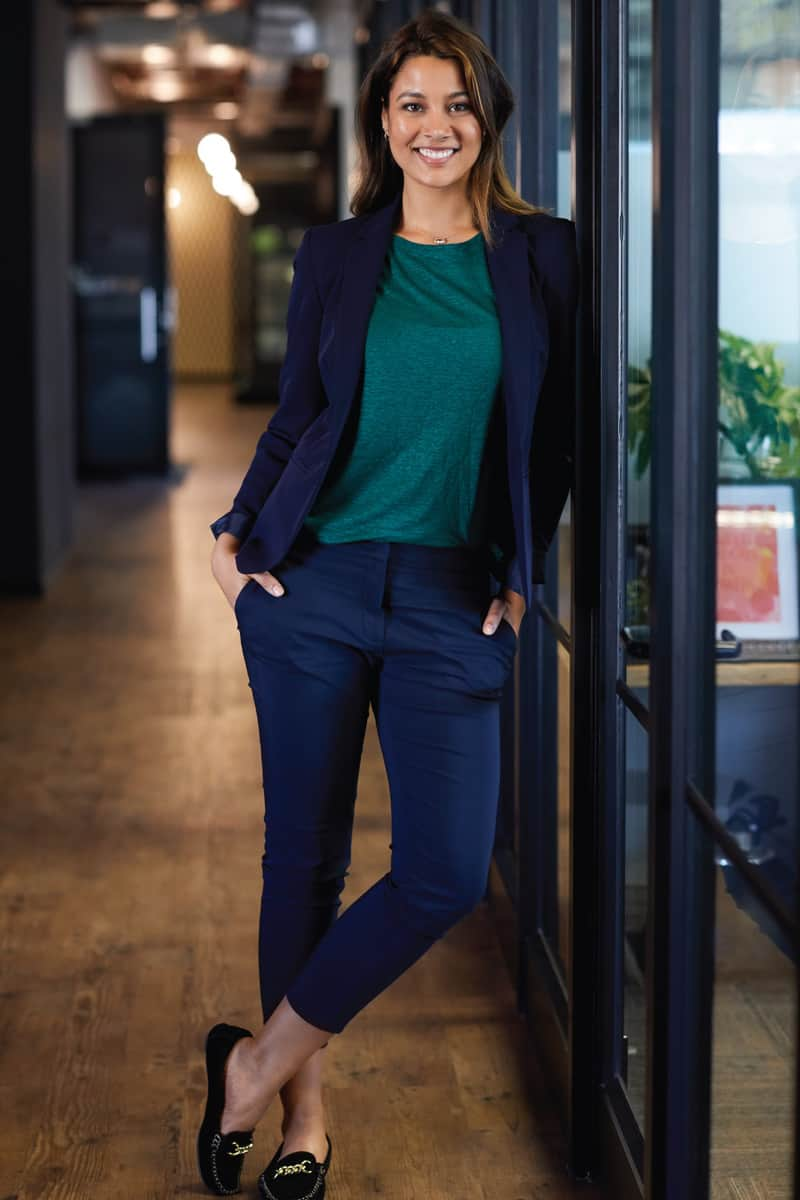 Full length of young businesswoman with hands in pockets leaning on wall