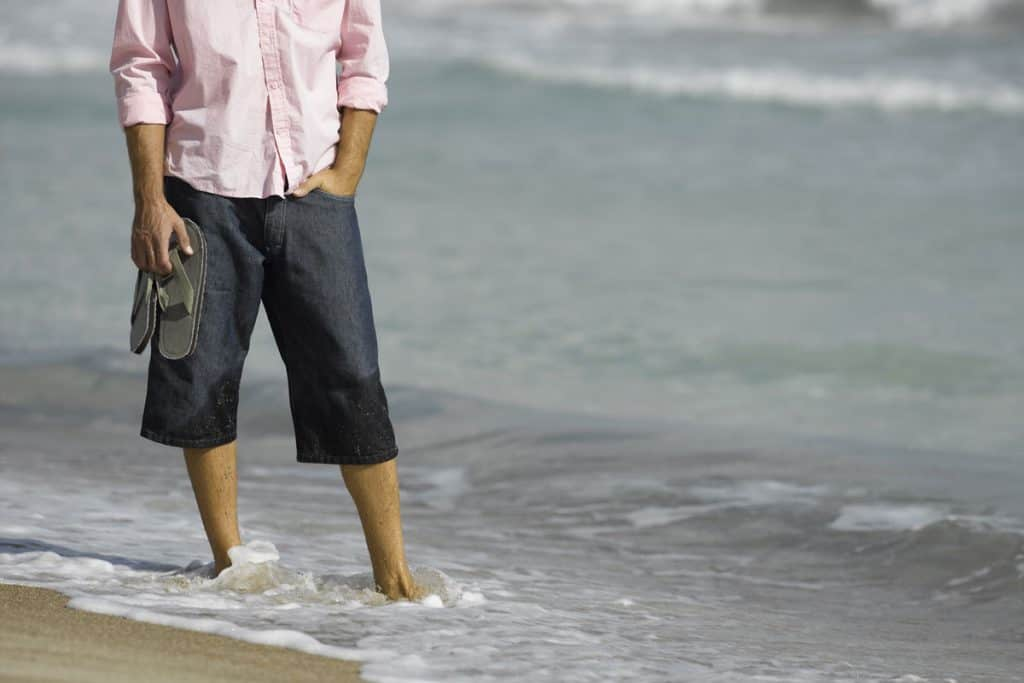 A man wearing a white top and semi wet Capri pants while standing on the shoreline while holding his sandals, Should Guys Wear Capri Pants?