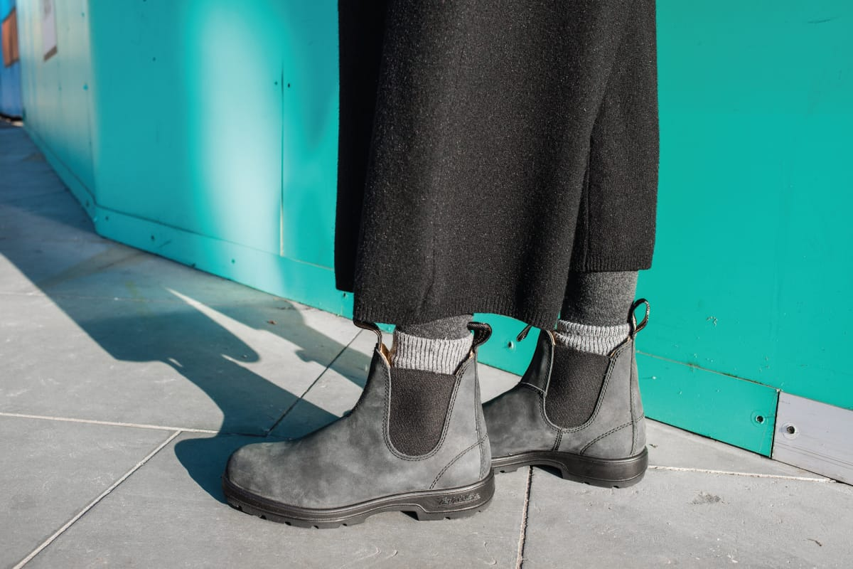 Woman wearing gray leather Chelsea boots standing on pavement, How To Wear Chelsea Boots (9 Suggestions For Women)