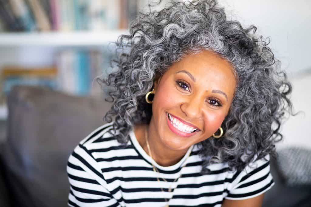 A beautiful black woman with makeup and white curly hair smiles for a headshot