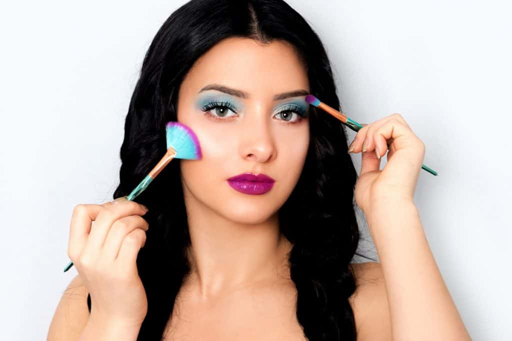 A beautiful woman putting on blue eyeshadow on her eyebrows while holding make up brushes on both her hands, What Color Lipstick Goes With Blue Eyeshadow?