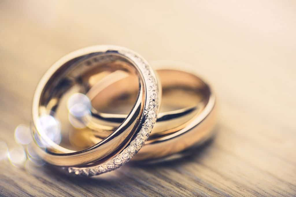 A golden ring encrusted with diamonds, How Many Grams Of Gold In A Ring [Typical Weights For Wedding Bands]