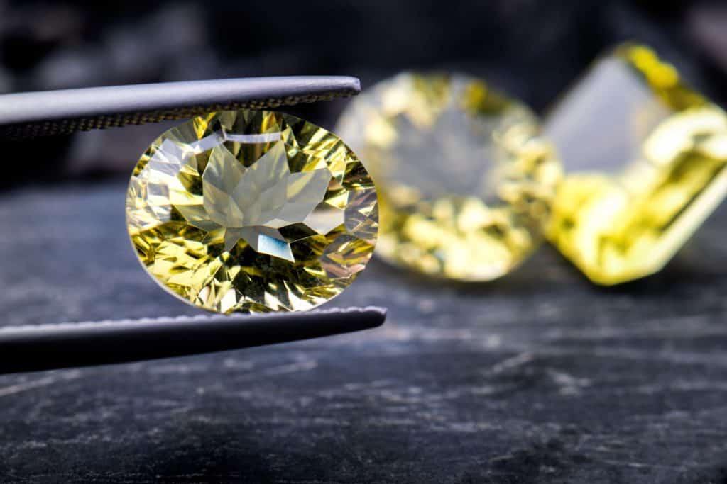 A gem cutter holding a lemon gem stone using pinchers