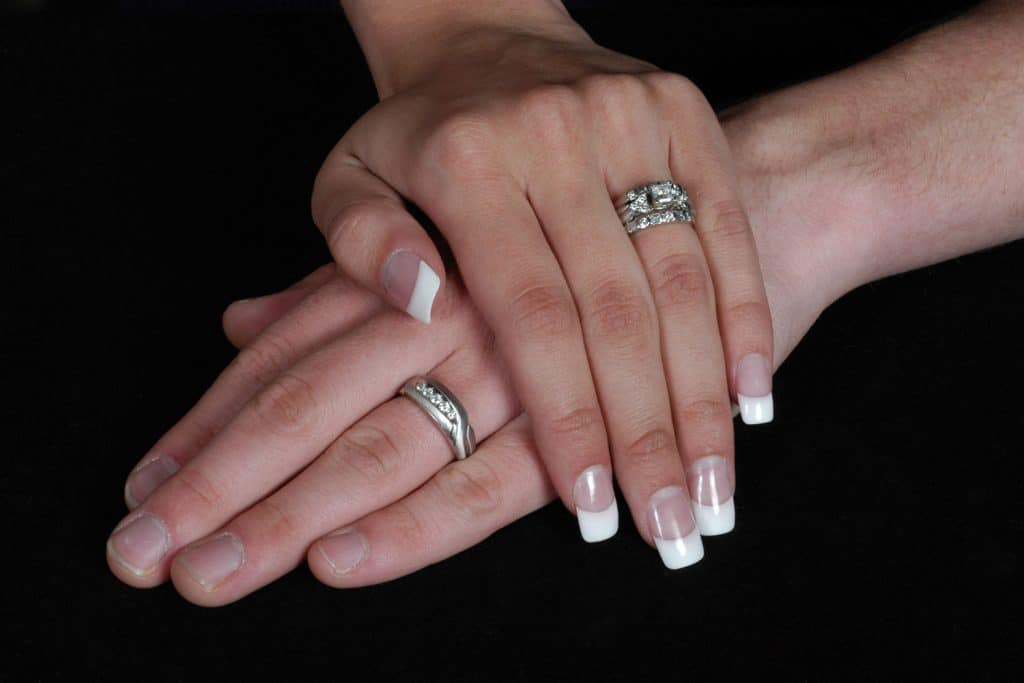 A new bride and groom place their hands together, showcasing a silver wedding rings