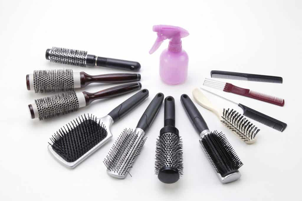 A spray bottle and spread of brushes. A great picture for cosmotology themed designs