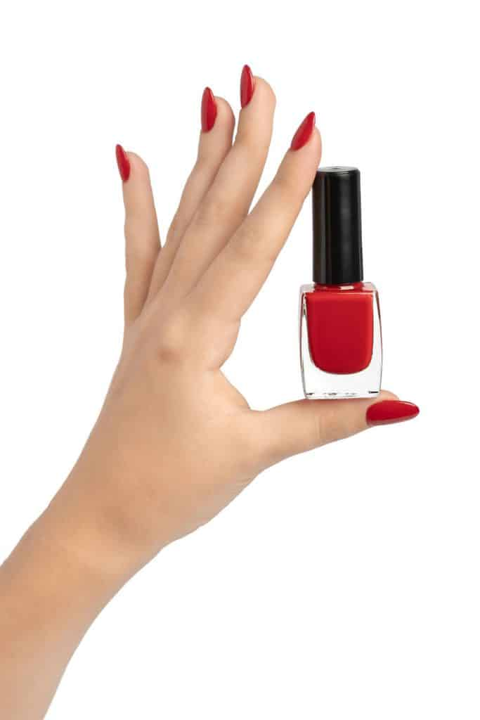 A woman holding a red nail polish in her hand