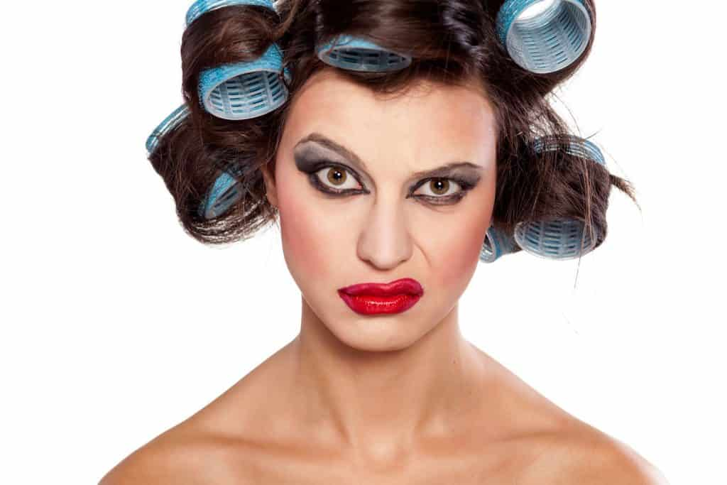 A woman looking weirdly at the camera with hair curlers on her hair