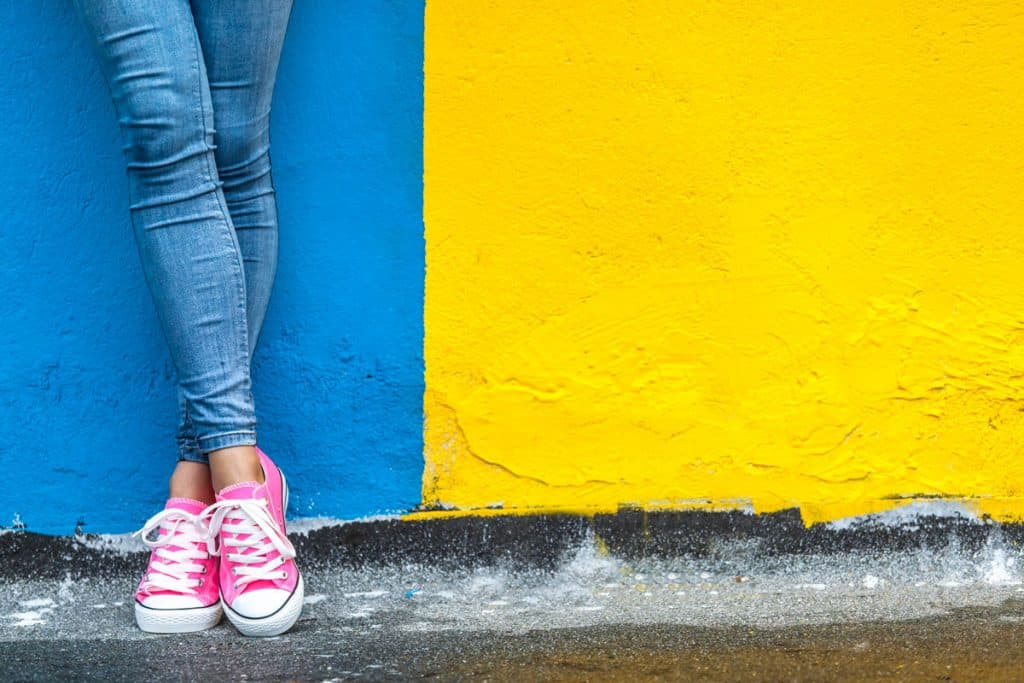 A woman wearing blue denim pants and pink sneakers, What Color Sneakers Go With Blue Jeans