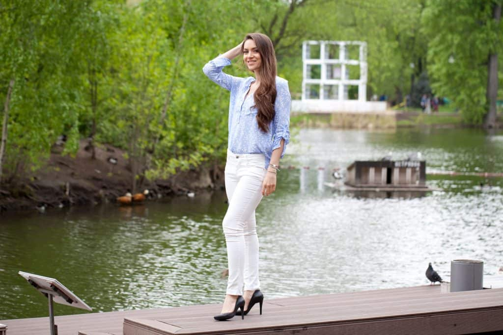 A woman wearing a blue shirt and white straight pants while standing on a platform of a river, How to Wear Straight Leg Pants