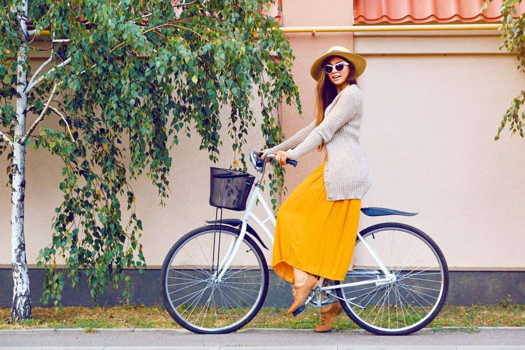 A woman wearing a yellow maxi dress while riding a bike, What Shoes To Wear With Maxi Dresses?