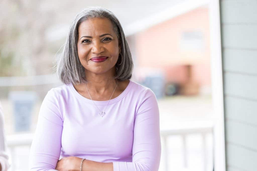 Beautiful African American senior woman with makeup stands confidently on her front porch. She is smiling at the camera.