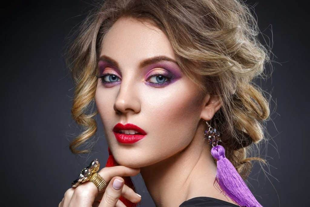 Beautiful blond young woman with bright purple makeup and tassel earrrings, What Color Lipstick Goes with Purple Eyeshadow?