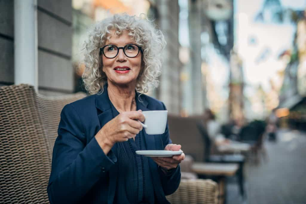 Beautiful senior woman with makeup drinking a hot drink in coffee shop