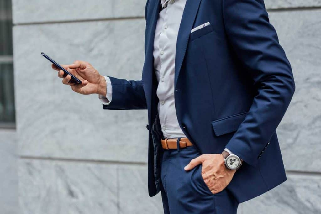 A businessman in a suit using his smartphone outdoors, Should Suit Jacket And Pants Match?