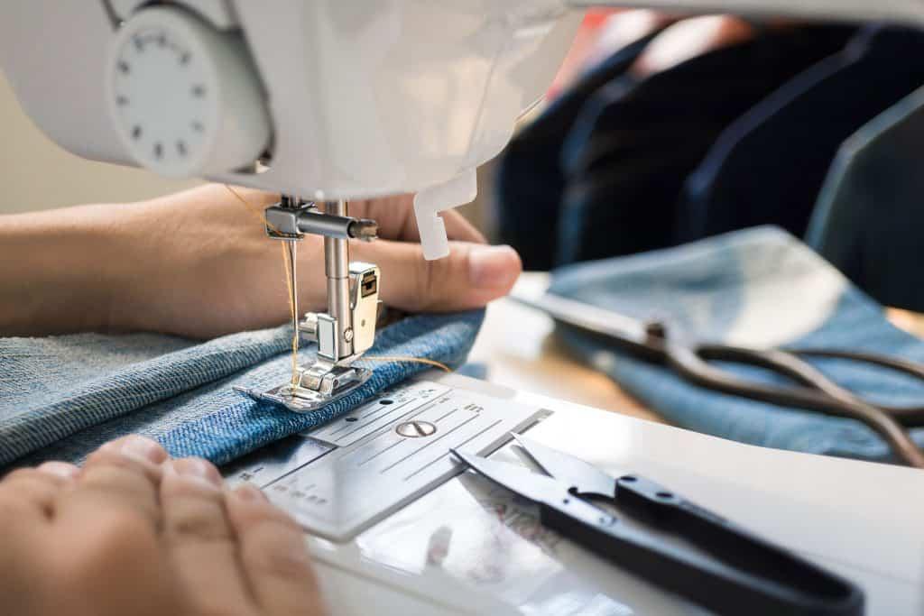 Closep up tailor process, women's hand working on sewing machine sew denim fabric