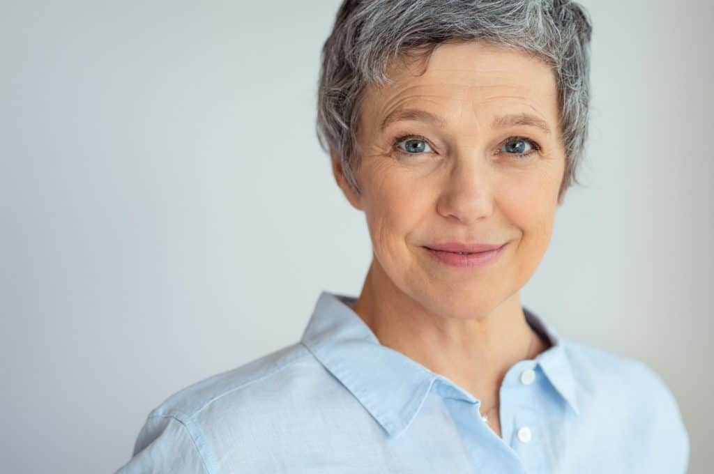 Closeup face of senior business woman with makeup standing against grey background with copy space