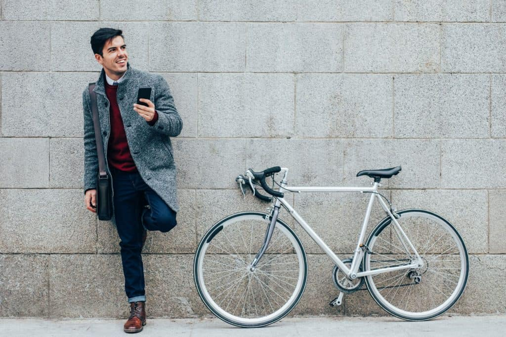 Elegant man with a bicycle using a smart phone in the city
