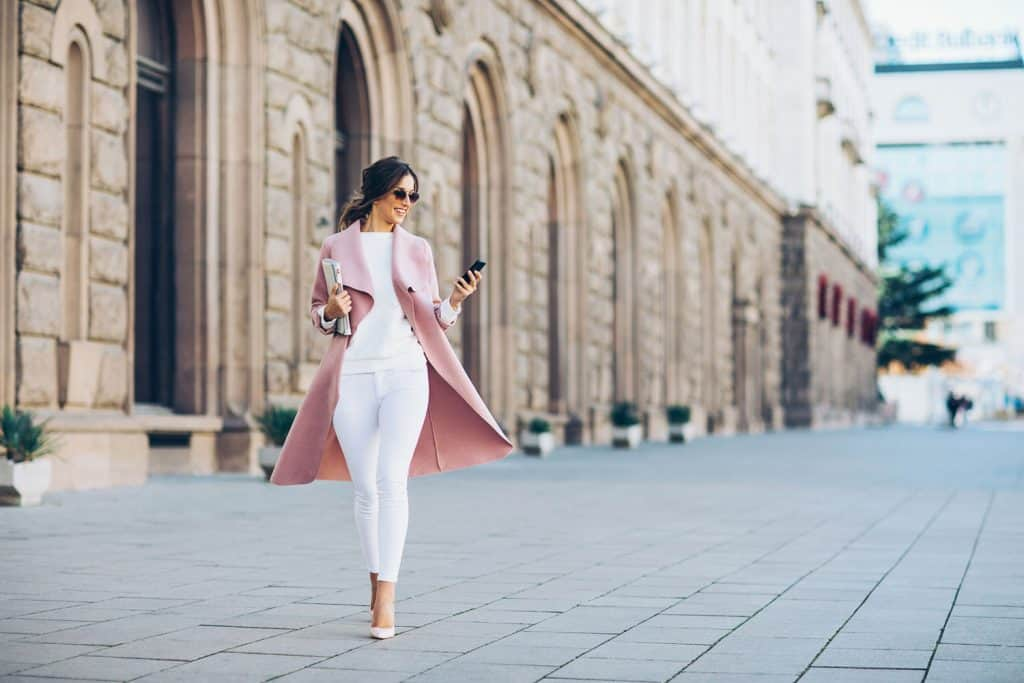 Elegant young woman walking on the square and texting in urban environment