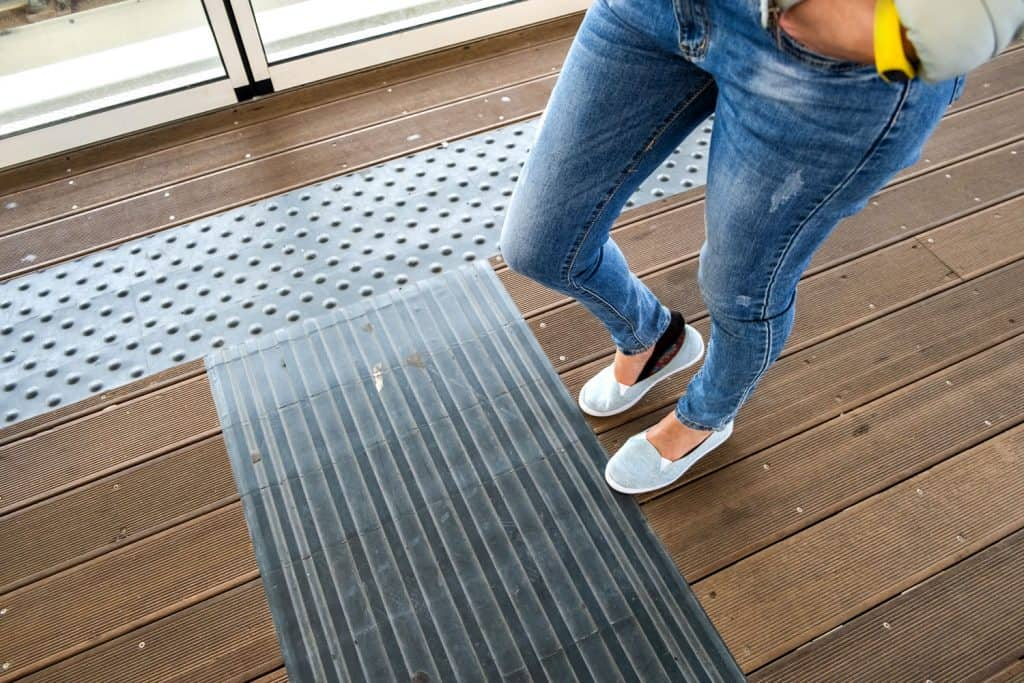 Female legs in denim jeans pants and light summer sneakers standing on wooden floor