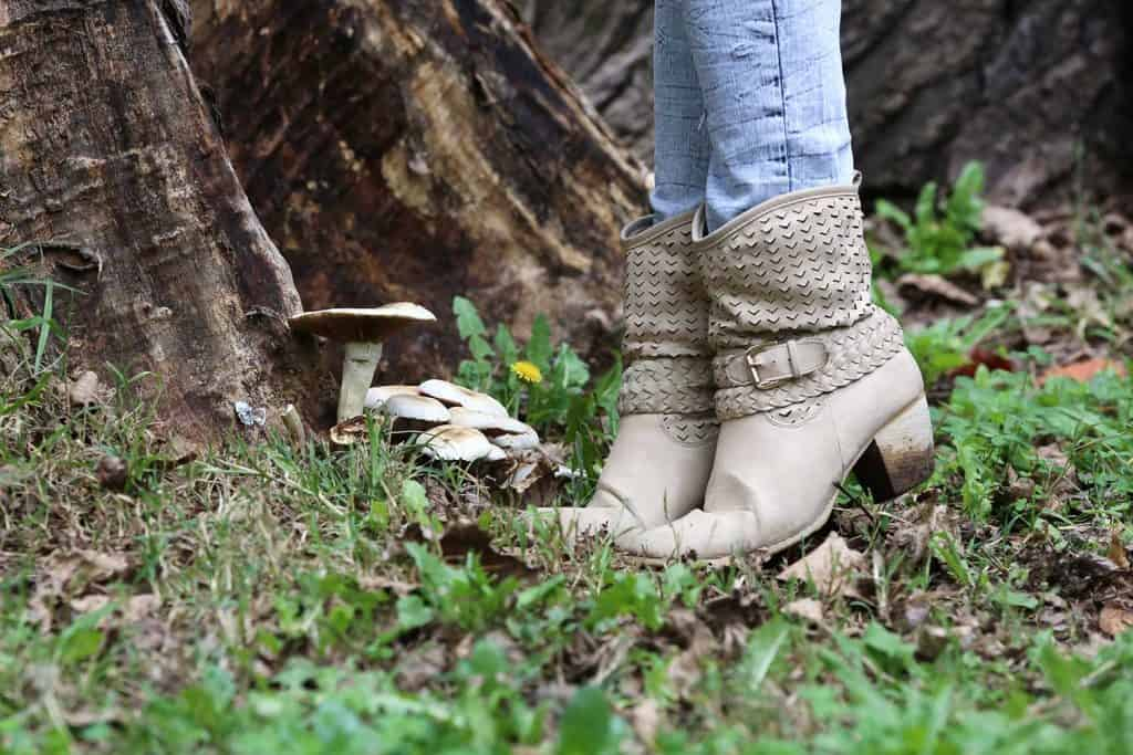 Female wearing ankle boots standing next to the forest mushrooms