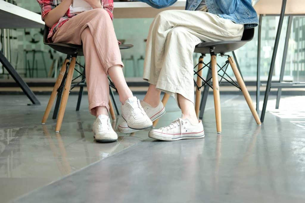 Girl teenager legs wearing sneakers sitting talking together