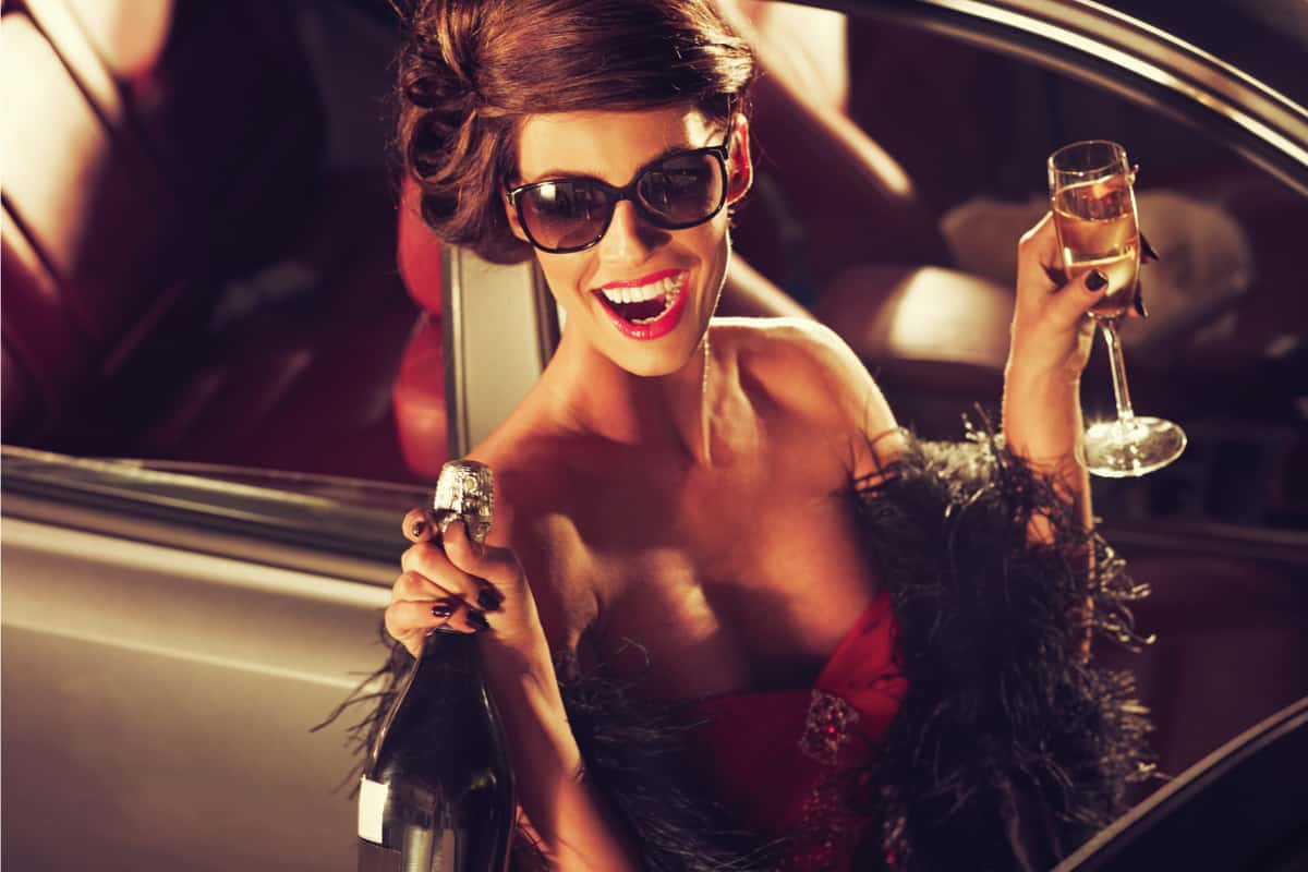 Glamorous brunette woman dressed in red evening gown with bleach feather and black nail color drinking champagne next to the car