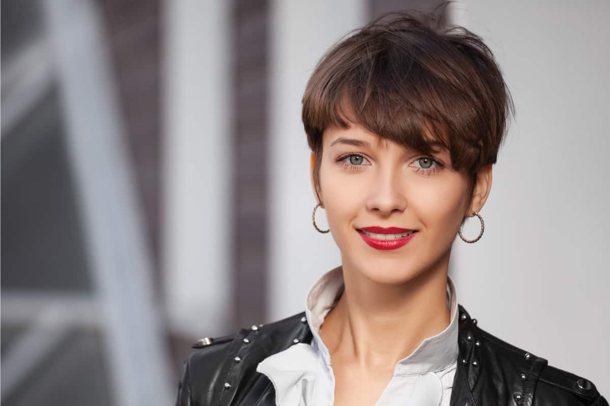 Happy young fashion woman in classic pixie cut and leather jacket walking in city street