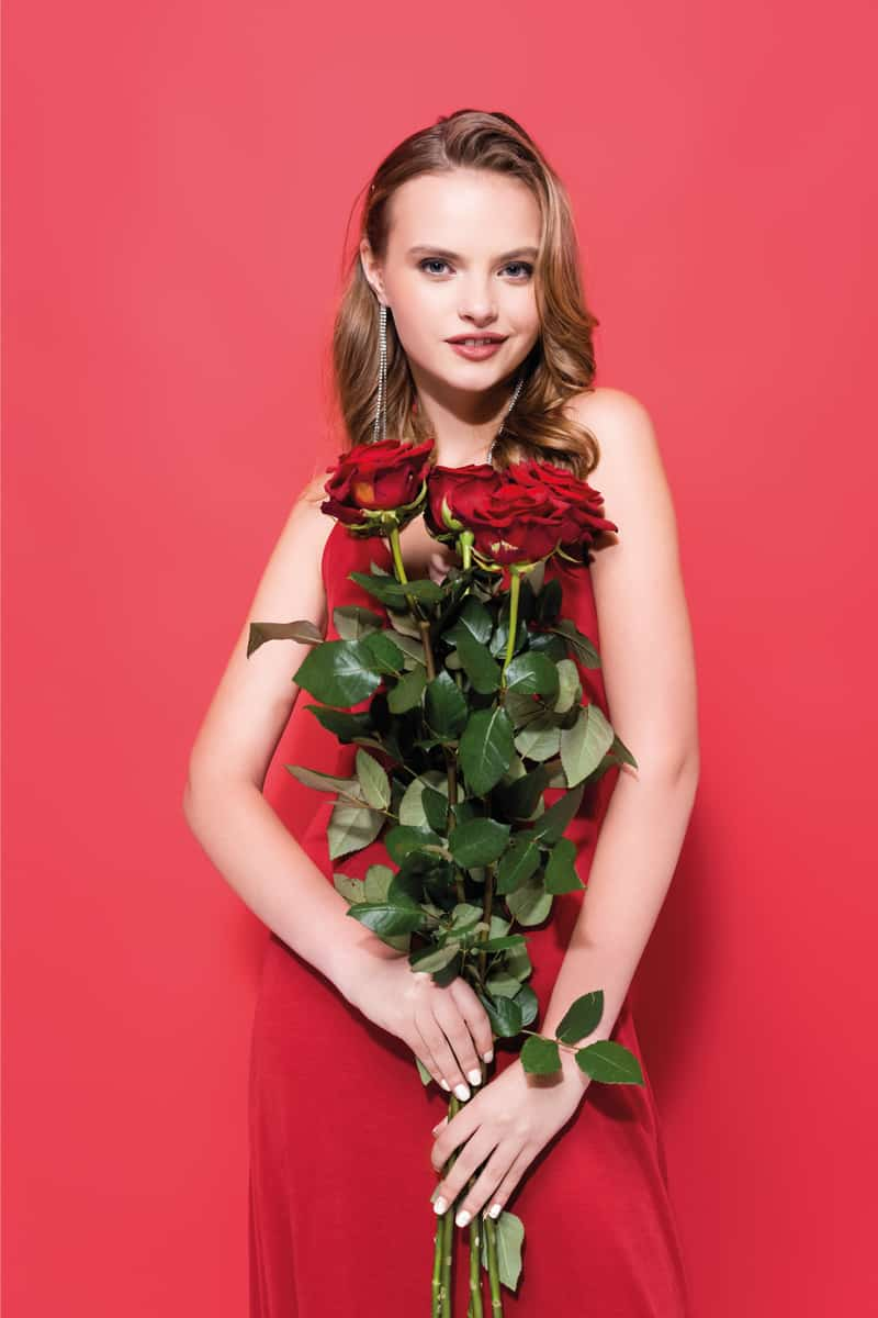 Happy young woman holding roses with nails in white