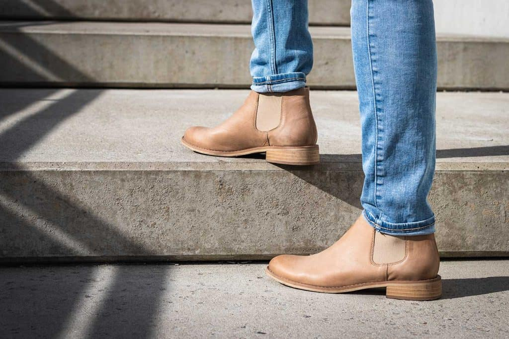 Legs in denim pants and leather boot on staircase