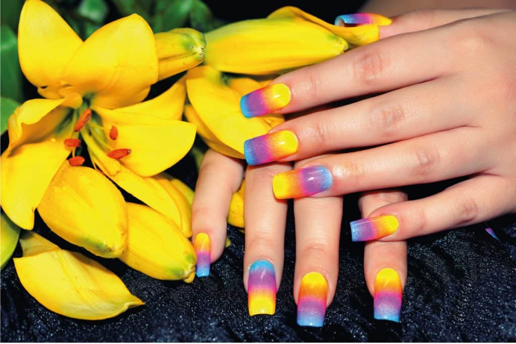 Female hands with colorful nail design holding beautiful yellow flower, What Color Nails With Red Dress?