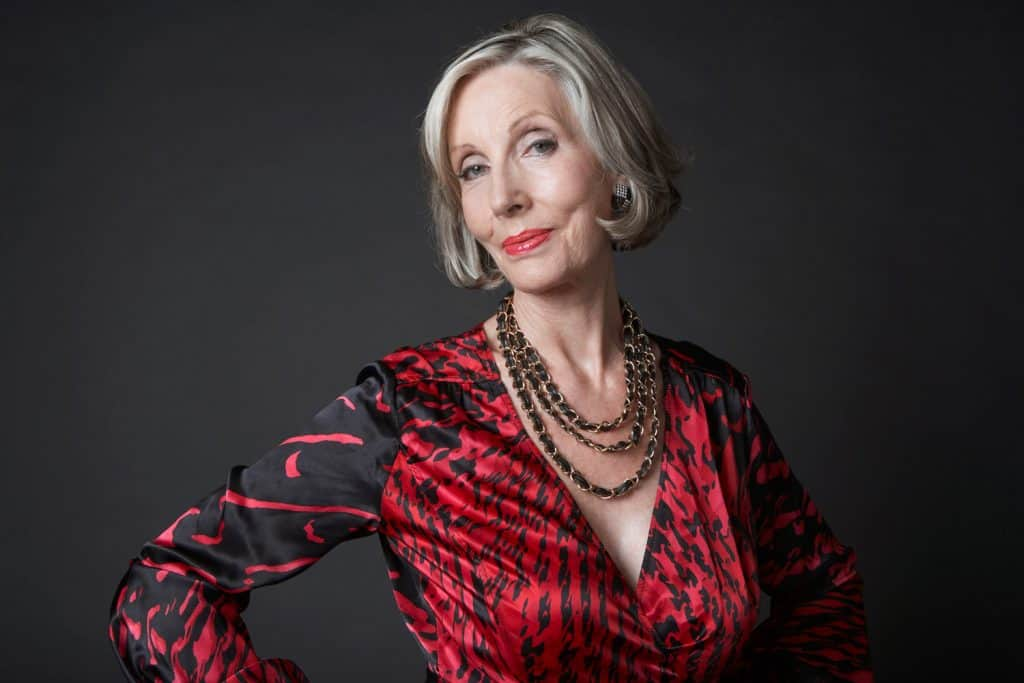 Portrait of a wealthy senior woman wearing makeup and necklace against black background