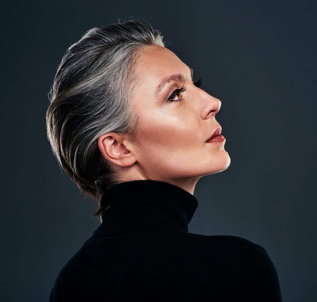 Studio-shot-of-a-beautiful-mature-woman-posing-against-a-dark-background