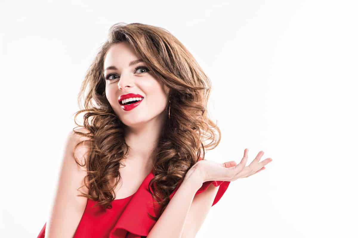 Surprised girl in red dress showing shrug gesture, makeup complimenting the red dress