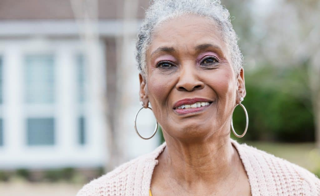 The-face-of-a-senior-African-American-woman-with-short,-gray-hair,-standing-outside-her-home.-She-is-smiling-and-looking-toward-the-camera.