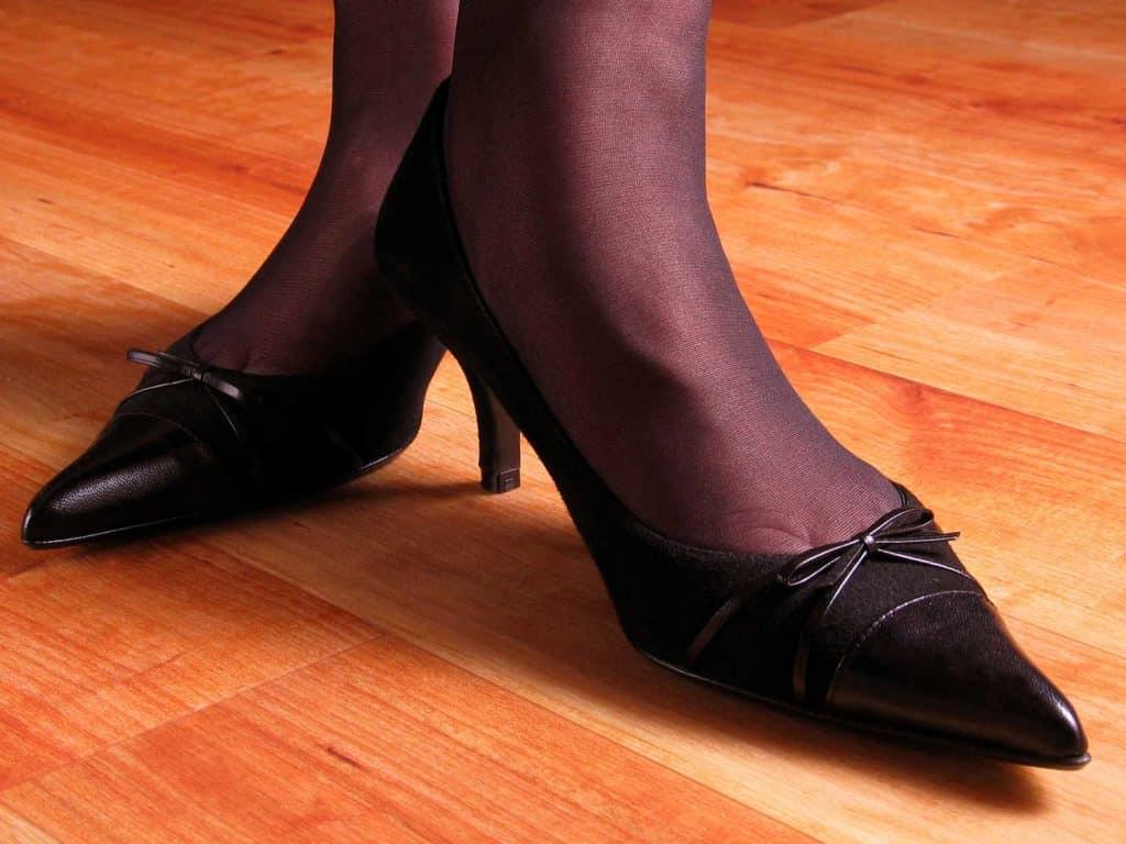 Woman's feet in black stockings and kitten heels on wooden floor