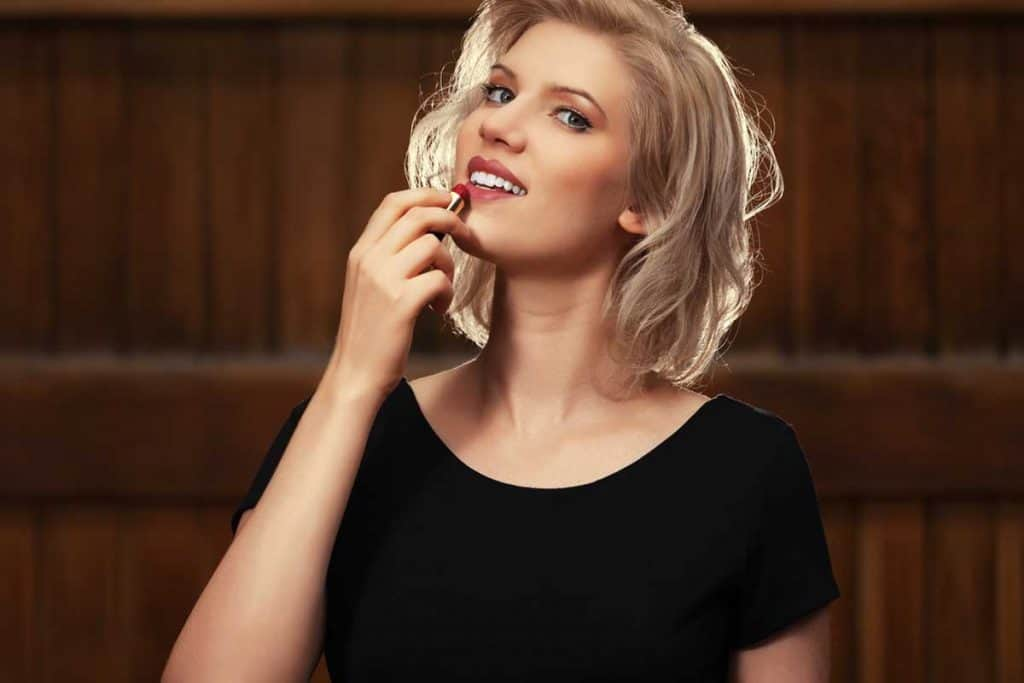 Young fashion blond woman in black dress putting lipstick on, What Color Lipstick to Wear With a Black Dress