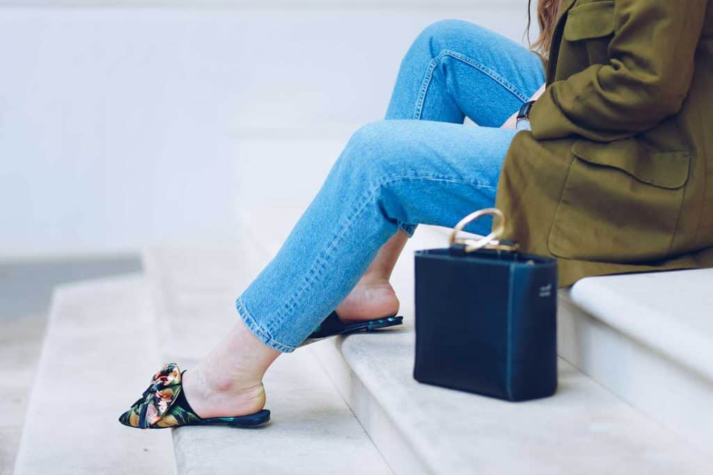 Young stylish woman wearing denim jeans and floral mules with a bow detail in front