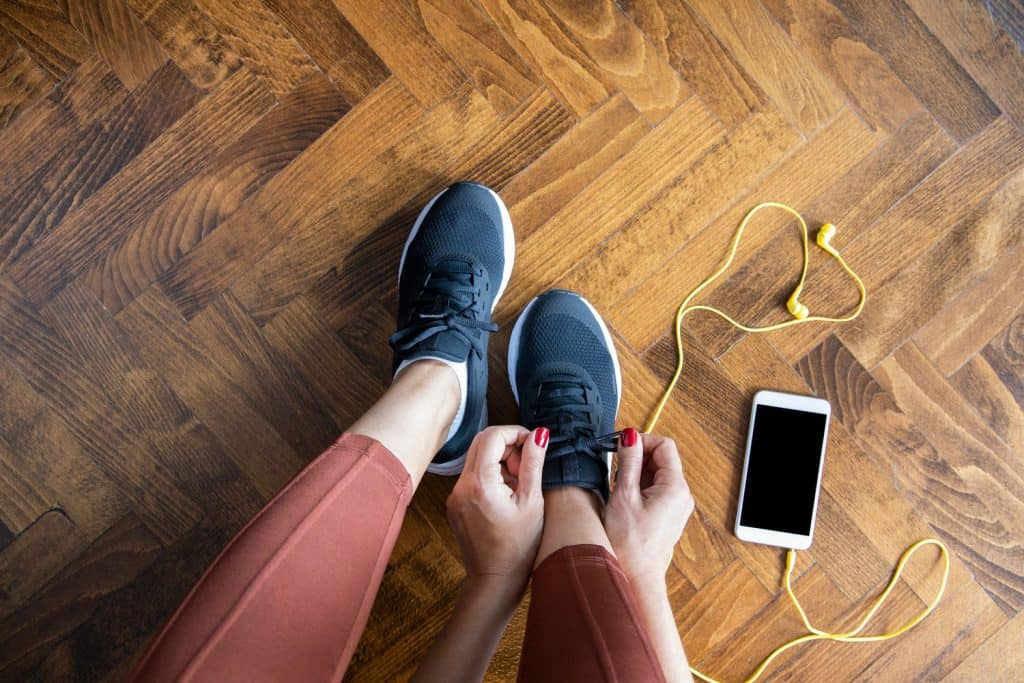 Young woman tying shoelace before workout, getting ready for jogging, Shoes Too Big? 7 Ways To Make Shoes Smaller