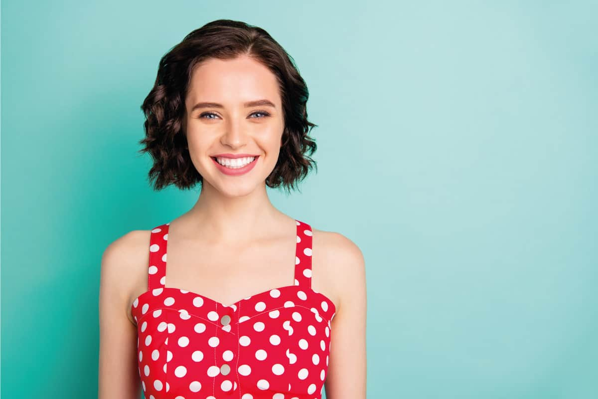 beautiful young woman in bob haircut wearing polka dots against teal background