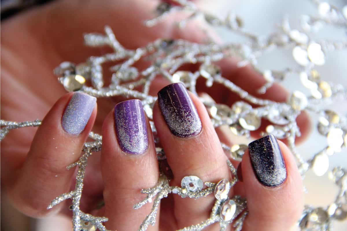 Female hand holding a glittery metal ornament, gradient nail color in violet and silver