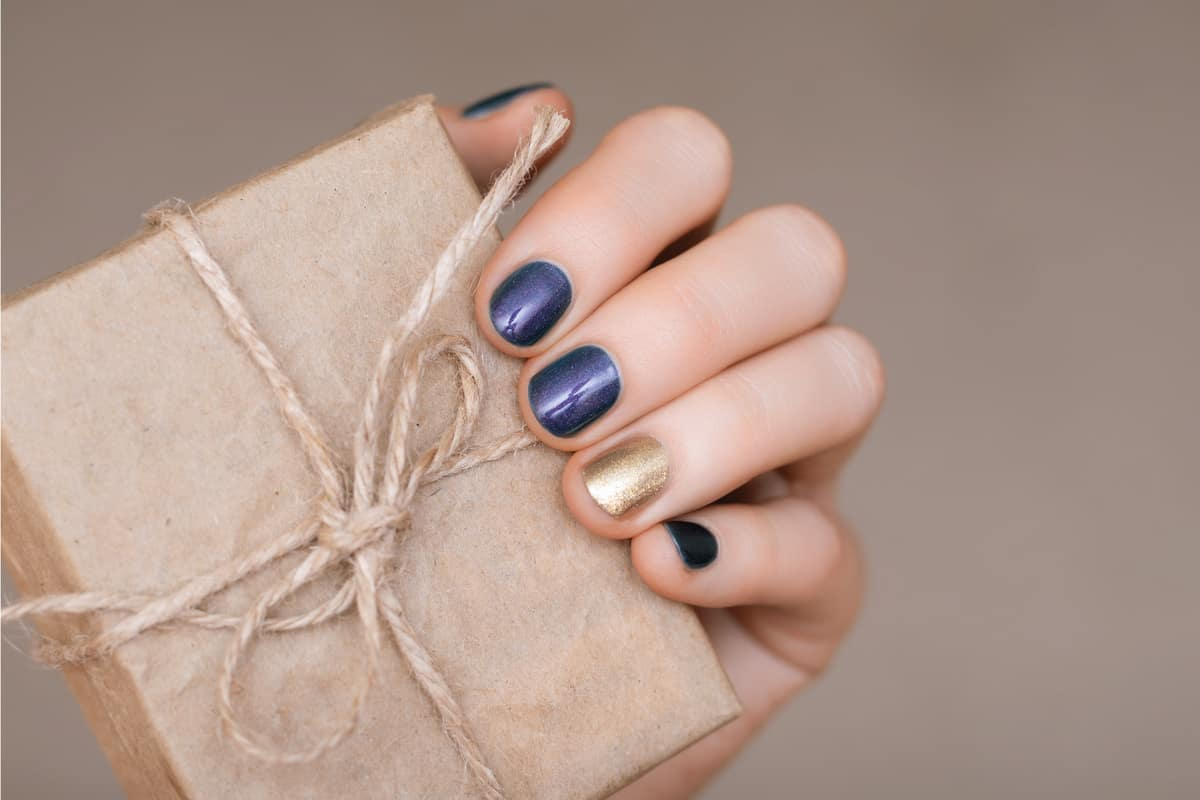 Female hand holding a rustic gift box, accent nail colors 4 in blue and 1 in gold
