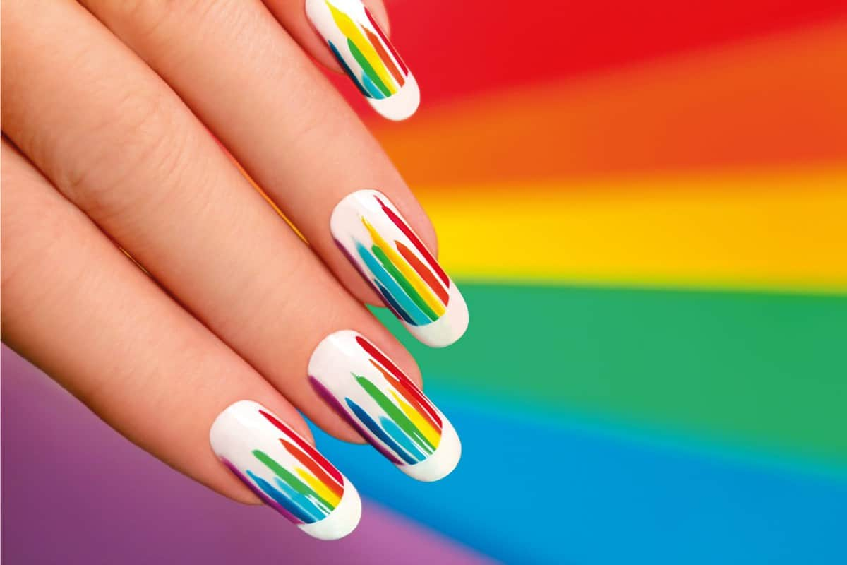 Female hand with rainbow nail color on a white base