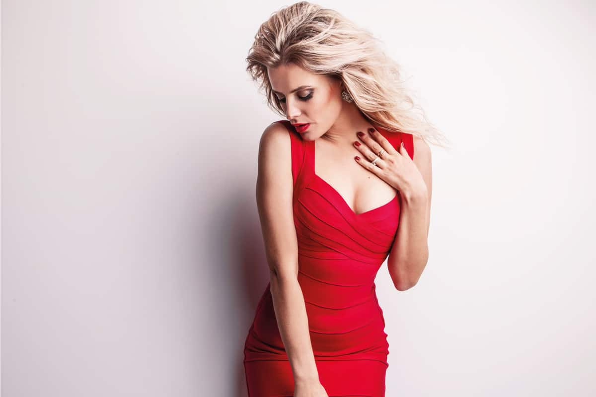 female model wearing an elegant red dress with matching red nail color