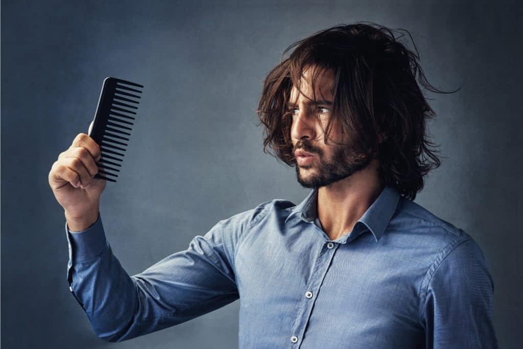 handsome young man looking at his comb while brushing his hair against a grey background