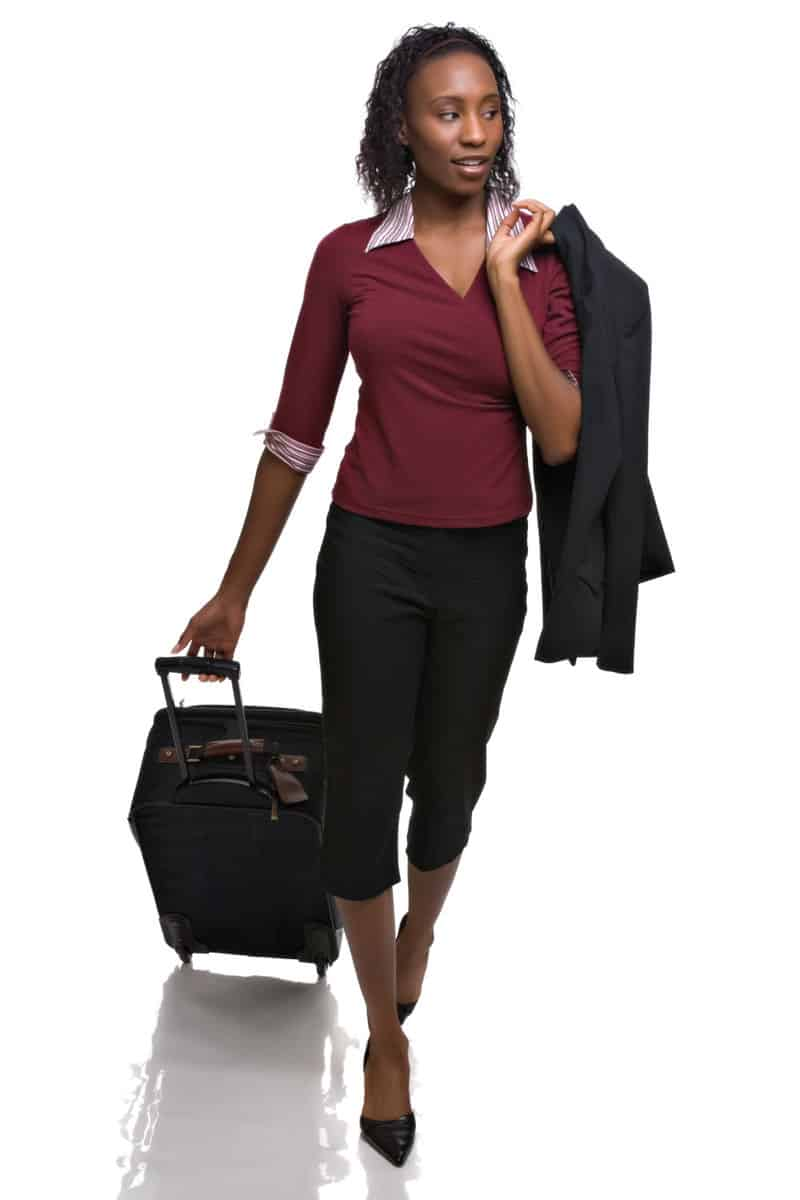 Lady with a trolley bag wearing a collared V-neck t-shirt and heels pair with business capris