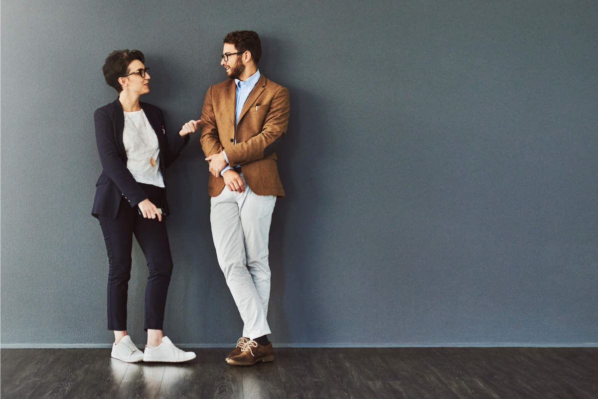 Man and woman in an office wearing a dark pair of capris with stylish blazer and sneakers for casual fridays