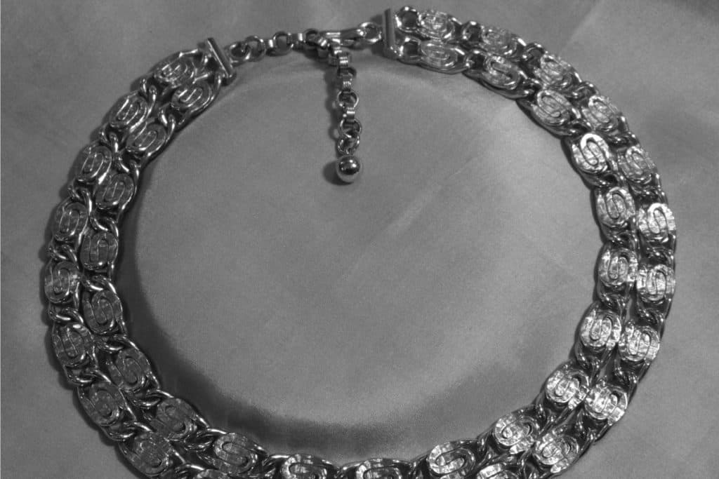 Rhodium plated necklace on a gray silk mat, Does Rhodium Plating Wear Off Jewelry?