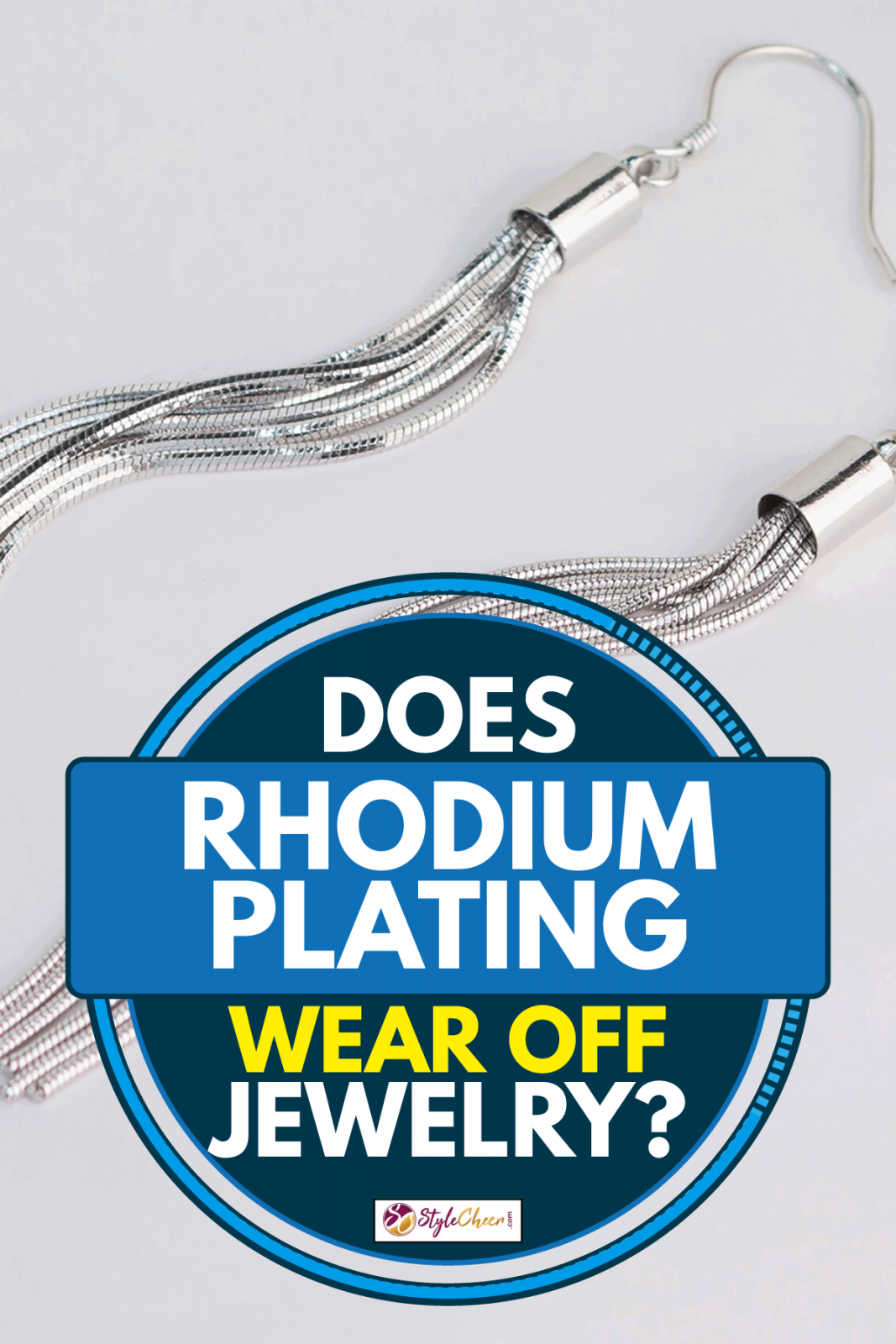Rhodium plated tassel earrings on a plain gray table, Does Rhodium Plating Wear Off Jewelry?